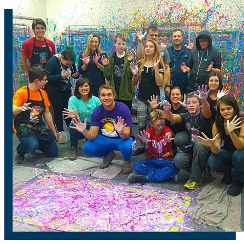 a group of happy young people are shown in a room with paint splattered all over the walls